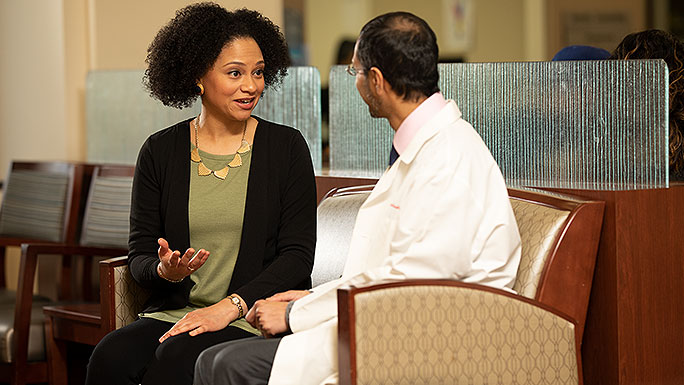 Reproductive endocrinologist Alberuni Zamah, MD, talking with a patient